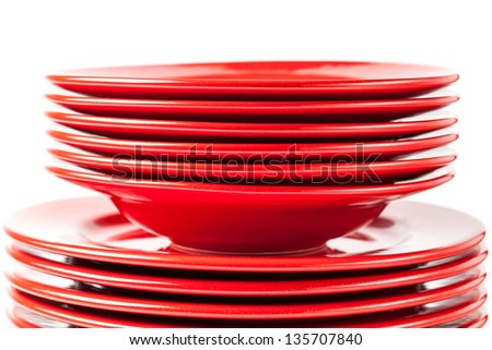 Stack of colorful red ceramics plates on white background - stock photo