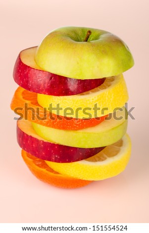 Stack of colorful sliced fruit with apple lemon orange