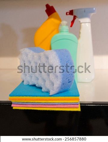 Stack of colorful soft absorbent kitchen cloths topped with a new sponge standing ready with cleaning supplies and detergents for household cleaning - stock photo