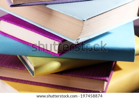 Stack of colourful hardback and paperback books, close-up - stock photo