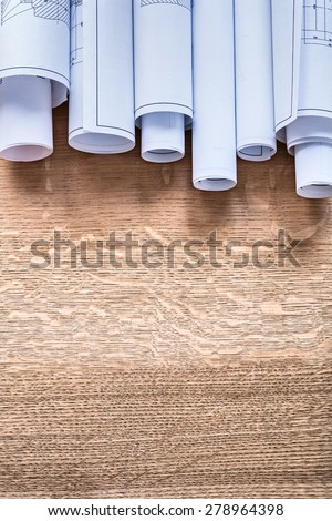 Stack of construction plans on wooden oaken board maintenance concept  - stock photo