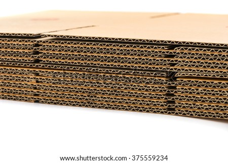 stack of corrugated cardboard boxes on white background. side perspective view of flattened boxes. - stock photo