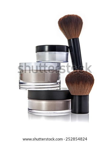Stack of cosmetic jars and brushes - stock photo