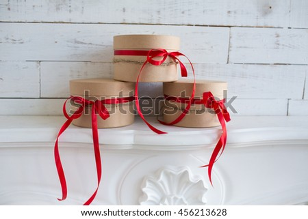 stack of craft round boxes with red ribbons