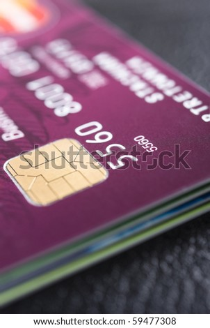 Stack of credit cards with details of a card with its chip and some numbers - stock photo