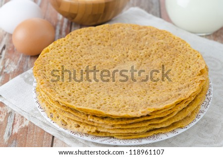 Stack of crepes made ??of corn flour on a plate and baking ingredients (eggs, flour, milk)