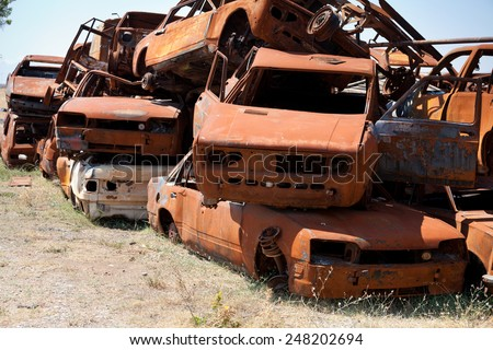 Stack of damaged rusted car scraps on junkyard - stock photo