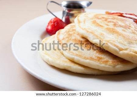 Stack of delicious pancakes with bacon, and a strawberry. Served with syrup