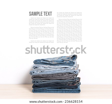stack of denim jeans isolate on wooden desk - stock photo