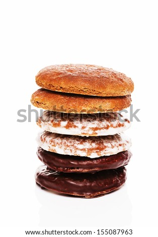stack of different lebkuchen gingerbread cookies with chocolate and other icing on white background