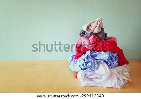stack of dirty clothes for laundry over wooden table. house choirs concept - stock photo
