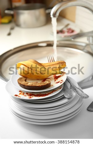 Stack of dirty plates near kitchen sink closeup - stock photo