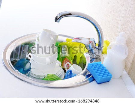 Stack of dishes soaking in kitchen sink - stock photo