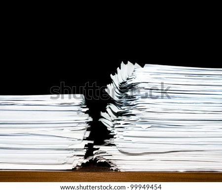 stack of documents or files, heap, overload of paperwork on black background - stock photo