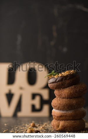 Stack of Donuts with crumbs, nuts and love sign on dark stone background - stock photo