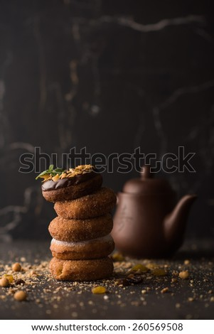 Stack of Donuts with crumbs, nuts and tea pot on dark stone background - stock photo