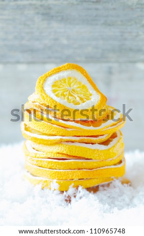 Stack of dried orange slices to season warm winter drinks and refreshments on a bed of snow with copyspace - stock photo