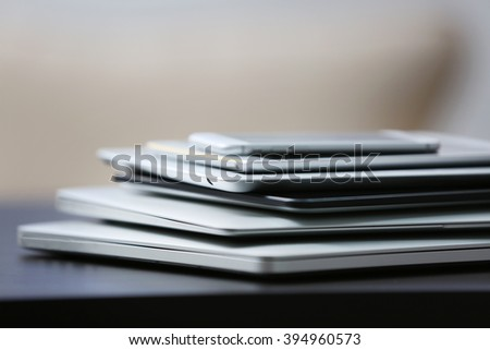 Stack of electronic devices on a dark desk