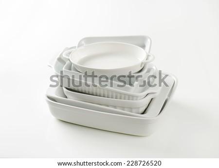 stack of empty baking trays on white background - stock photo