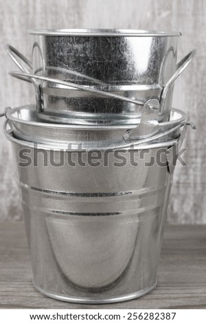 Stack of empty galvanized buckets on rustic wooden background.
