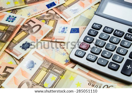 stack of 50 Euro money and calculator