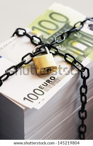 Stack of Euros secured by padlock and chain - stock photo
