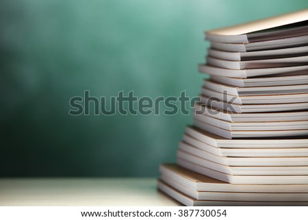 stack of exercise book in front of chalkboard - stock photo