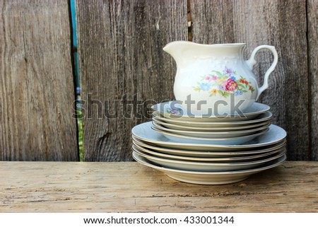 Stack of fine porcelain plates decorated with floral pattern and small jug with old grunge wooden background behind. Vintage kitchen ware in a rustic setting - stock photo