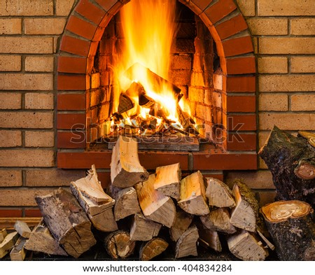 stack of firewood and fire in indoor brick fireplace in country cottage