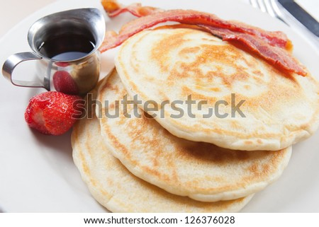 Stack of fluffy made-from-scratch pancakes with bacon and strawberry