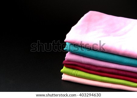 Stack of  folded fabric on black background. copyspace for fabric conceptual - stock photo
