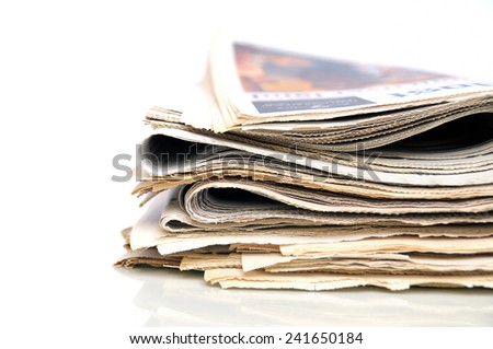 Stack of folded newspapers on white background - stock photo