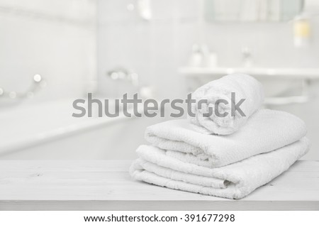 Stack of folded white spa towels over blurred bathroom background - stock photo