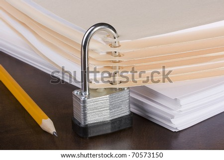Stack of folders closed by a metal lock. - stock photo