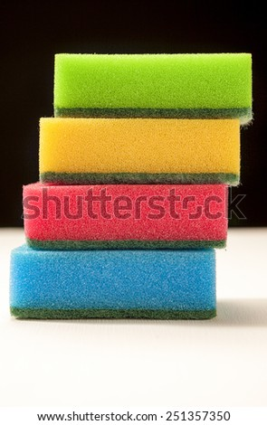 Stack of Four Color Kitchen Sponges Laid On White Surface Against Black Background. Vertical Image Composition - stock photo