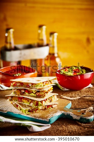 Stack of four quesadilla wedges on wooden cutting board next to guacamole bowl and beer bottles in background - stock photo