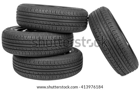 Stack of four wheel new black tyres, isolated on white background - stock photo