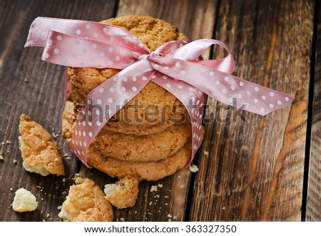 stack of fresh baked cookies with rose bow closeup on wooden background  - stock photo