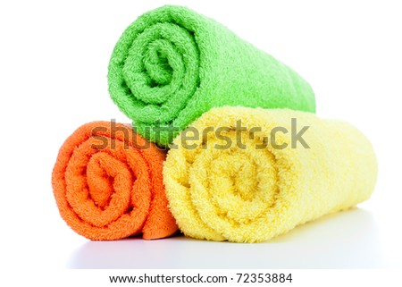 stack of fresh colorful towels rolls isolated - stock photo