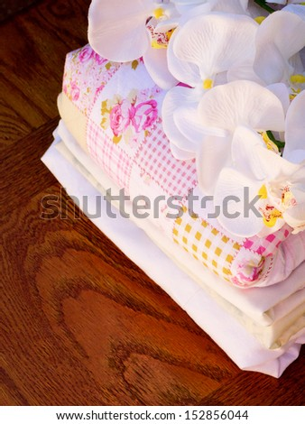 Stack of fresh laundry with a sprig of flowers on top
