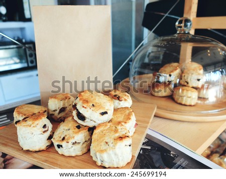 Stack of fresh scones on tray with paper bag, retro filter effect - stock photo