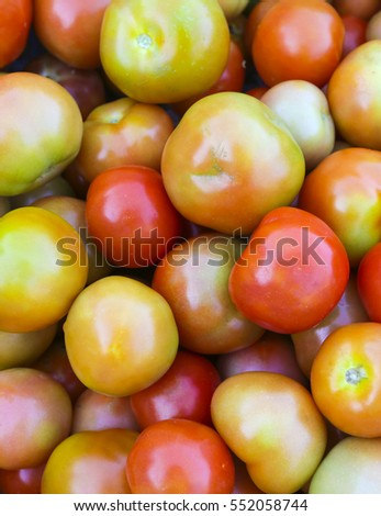 Stack of fresh tomatoes on display at market.