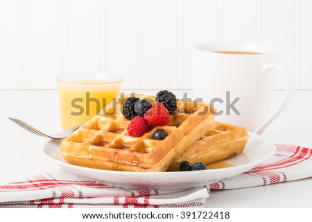 Stack of fresh waffles with maple syrup and fruit. - stock photo