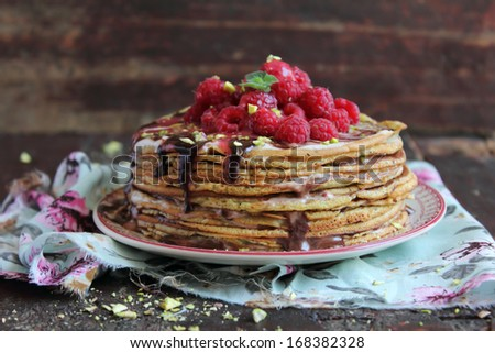 Stack of freshly baked pancakes with chocolate sauce and raspberry perfect for traditional russian holiday pancake week - stock photo