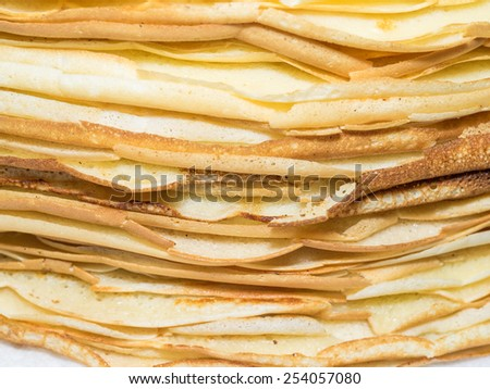 Stack of freshly made and still warm homemade crepes. - stock photo