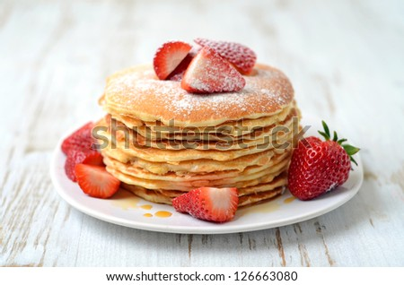 stack of freshly prepared traditional pancakes with strawberries - stock photo