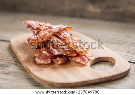 Stack of fried bacon strips on the wooden board - stock photo