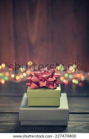 Stack of gift boxes with red bow over wooden background - stock photo