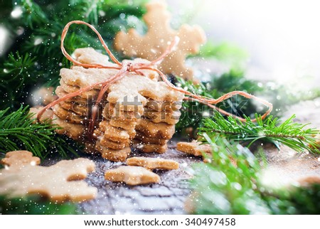 Stack of Ginger Cookies Snowflakes tied up by a Rope in Christmas Composition Decorated with Fir Tree. Illustrated with Drawn Snow - stock photo