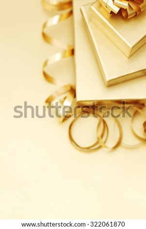 Stack of gold christmas gift boxes with bow and ribbon - stock photo